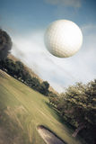 Golf ball flying over a green field Stock Image
