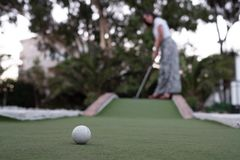 Shoot of a woman playing minigolf with the ball in the foreground royalty free stock images