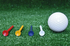 Golf ball and four tees Royalty Free Stock Image