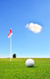 Golf ball in front of flag royalty free stock image