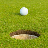 Golf ball in front of the hole, focus on the hole Stock Images
