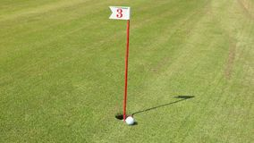 Golf ball goes into the hole stock footage