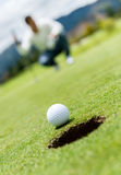 Golf ball going into a hole Royalty Free Stock Image