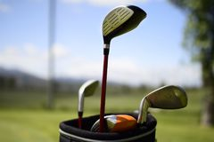 Golf ball and golf club in bag on green grass royalty free stock photography