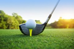 Golf ball and golf club in beautiful golf course with sunset bac stock image