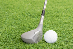 Golf ball and golf club on green grass Stock Images