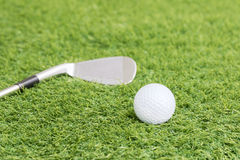 Golf ball and golf club on green grass Royalty Free Stock Photos