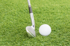 Golf ball and golf club on green grass Royalty Free Stock Image
