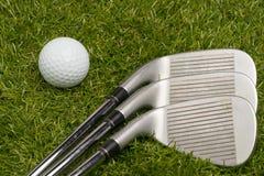 Golf ball and golf clubs Stock Photos