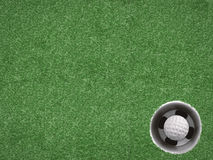 Golf ball in golf cup on green. Top view Stock Photo