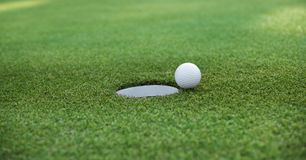 Golf ball and golf hole on green grass with copy space royalty free stock images
