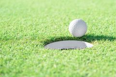 Golf ball and golf hole on green grass with copy space royalty free stock photography