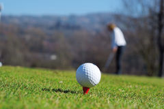 Golf ball and golf player. Golf ball on a putting training green with golf palyer on the background Stock Images
