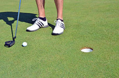 Golf ball golf shoes and stick Royalty Free Stock Photography