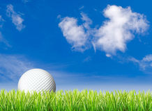 Golf ball, grass and blue sky Stock Photos
