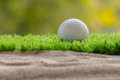 Golf ball on grass close sand bunker Stock Images