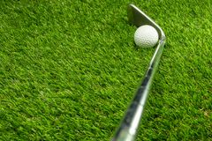 Golf ball and golf club on grass royalty free stock photography
