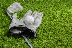Golf ball and club on grass stock image