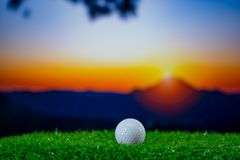 Golf ball on grass on hills sunset stock images