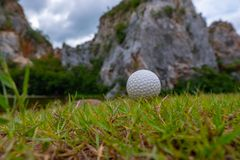 Golf ball on grass near  mountain royalty free stock images