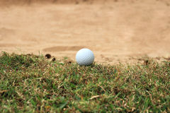 Golf ball on grass near sand Stock Photo