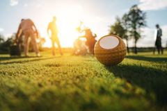 Golf ball on grass and silhouettes of golfers playing behind. Close-up view of golf ball on grass and silhouettes of golfers playing behind Royalty Free Stock Images