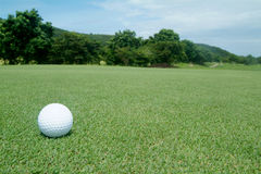 Golf-ball on green. With scenery in the background Royalty Free Stock Images
