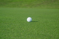 Golf ball on the green. Casting a long shadow Stock Photo