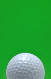 Golf Ball with Green Background. Golf Ball isolated on a green background, copy space, vertical Stock Images