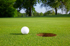 Golf ball on the green. Close to the hole Royalty Free Stock Photos