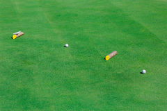 Golf ball on green course field. Golf ball on perfect wavy green ground on a golf course Royalty Free Stock Image