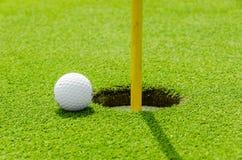 Golf ball on green fairway on the lip. Golf ball on green fairway blue cloudy summer sky in the background stock photography