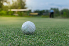 Golf ball on green and Golf player Royalty Free Stock Images