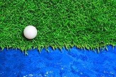 Golf ball on green grass. Near blue water Stock Photography