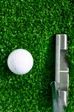 Golf ball on green grass. Golf ball and putter on green grass stock photos