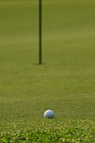 Golf ball on green grass. With flag pillar in background Stock Photos