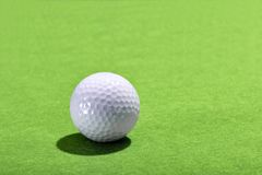 Golf ball on a green grass background. Golf ball casting a backlit shadow on a green grass or baize background with copy space Stock Images