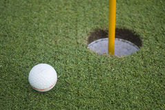 Golf ball on green grass in front of hole Royalty Free Stock Photo