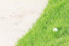 Golf ball on green grass near sand bunker stock photography