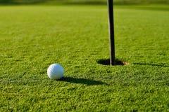 Golf ball on the green. Golf ball on the green grass near to pitch Stock Photos