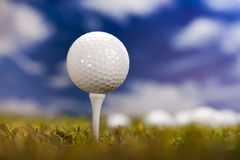 Golf ball on green grass over a blue sky Royalty Free Stock Photo