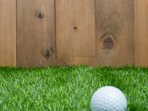 Golf and ball on green grass and wood background.  Stock Photo