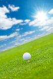 Golf ball on the green lawn. With cloudy sky Royalty Free Stock Photo