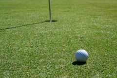 Golf Ball on green near hole. A Golf Ball on green near hole with flag pole royalty free stock image