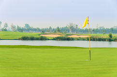 Golf ball on green near hole with yellow flag. With water and sand bunker in background Royalty Free Stock Photo