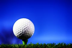 Golf ball on green tee on golf course Stock Images