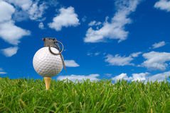 Golf ball grenade. From the ground level with grass and cloudy sky Stock Image