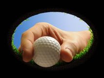 Golf ball with hand. Hand taking a golf ball out of a golf hole seen from below Royalty Free Stock Image