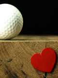 Golf ball and heart on the edge of table. Royalty Free Stock Photography