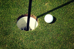 Golf Ball at Hole. A golf ball sits next to the hole on a golf course Stock Images